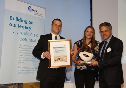 Simon Wiltshire, left, biodiversity and restoration advisor for Aggregate Industries, and Alexandra Pick, Hanson UK's landscape manager receive the award from Alan Law, chief strategy and reform officer for Natural England.
